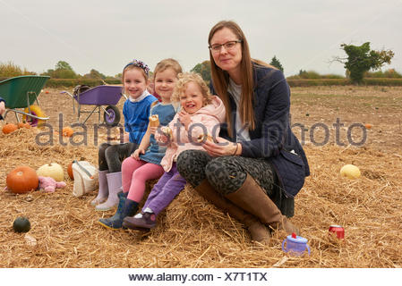 Portrait of mid adult woman and three girls picnicking in pumpkin field - Stock Photo