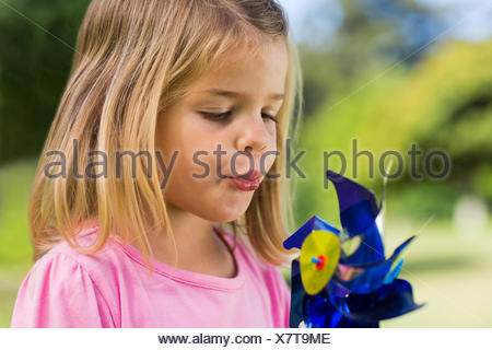 Cute girl blowing pinwheel at park - Stock Photo