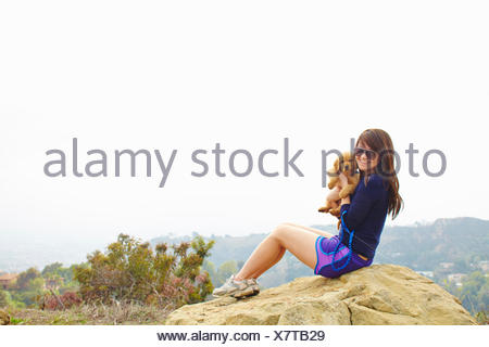Young woman sitting on rock, holding labrador puppy - Stock Photo
