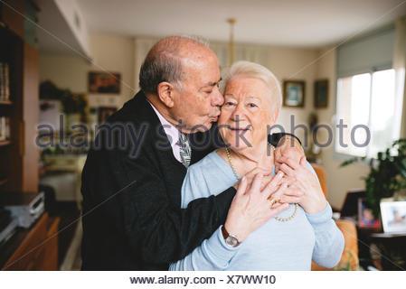 Senior couple hugging and kissing at home - Stock Photo