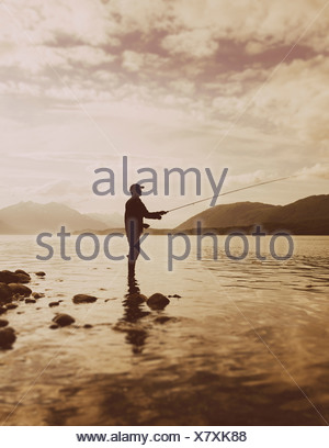 Silhouette of a man fly-fishing in calm waters on the Waschusett inlet in Glacier Bay national park in Alaska - Stock Photo