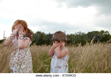 Two little girls playing hide and seek in a field - Stock Photo
