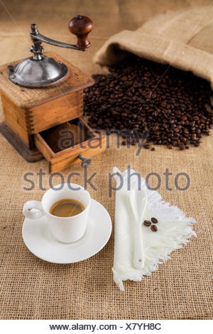 Coffee with mill and beans on jute - Stock Photo