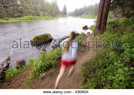 A woman runs along the Deschutes River Trail near downtown Bend, Oregon. (motion blur) - Stock Photo