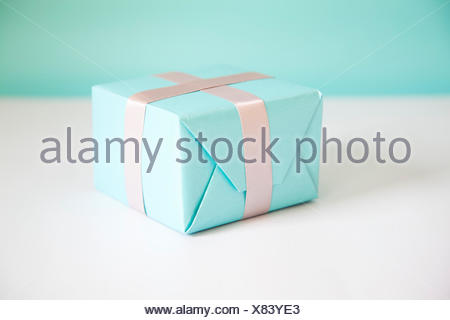 Gift box wrapped in blue paper - Stock Photo