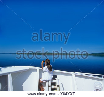 Young girl Birdwatching on deck of Coastal Boat, Cartwright, Labrador, Canada. - Stock Photo