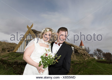 Newlywed couple smiling in field - Stock Photo