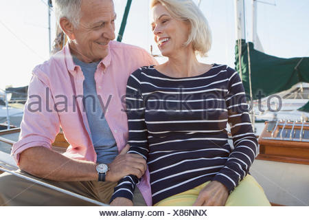 senior couple looking at each other on sailboat - Stock Photo