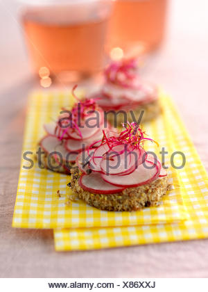 Radishes on sliced brown bread - Stock Photo