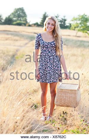 USA, Washington, Seattle, Happy teenage girl (16-17) standing in meadow, holding picnic basket - Stock Photo