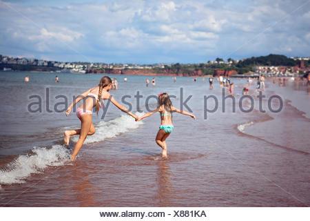 Two girl (4-5, 12-13) running along beach - Stock Photo