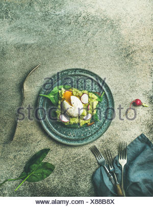 Healthy vegetarian breakfast flat-lay. Wholegrain toast with avocado, spinach and poached egg on plate over grey concrete background, top view, copy s - Stock Photo