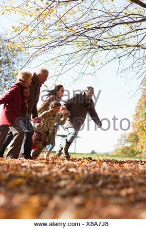 Extended family running in park - Stock Photo