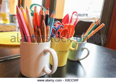 Assortment of scissors and Colored drawing pencils in a variety of colors on desk - Stock Photo