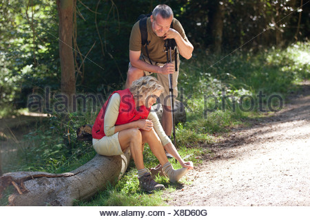 A mature couple resting beside a country path, woman massaging her sore feet - Stock Photo