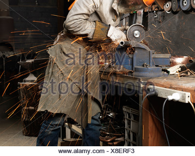 Blacksmith grinding metal on a machine in workshop - Stock Photo