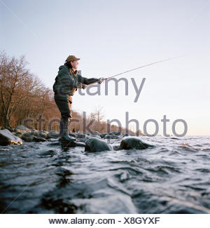 Man fishing by the sea, Sweden. - Stock Photo
