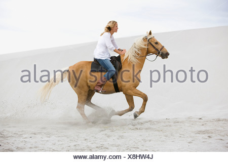 Girl riding horse on the beach - Stock Photo