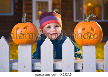 Infant Girl Peeks Between Jack-O-Lantern Faces Stuck On Top Of The Fence Boards, House In Background At Twilight, Alaska. - Stock Photo