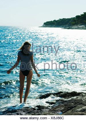 Young woman walking in sea, Dubrovnik, Croatia - Stock Photo