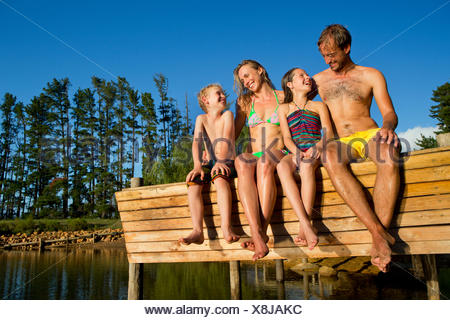 Portrait of happy family sat on jetty beside lake - Stock Photo