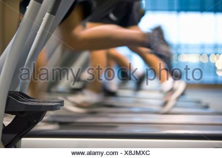 Legs running on treadmills in health club - Stock Photo