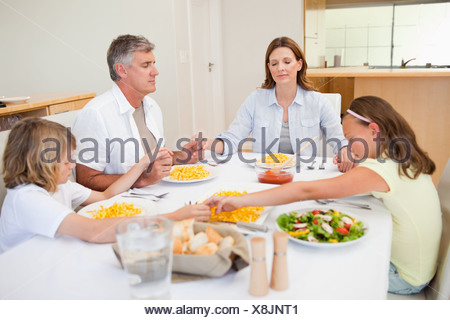 Family saying grace - Stock Photo
