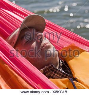 A man lying in a hammock - Stock Photo