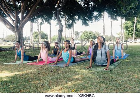 Schoolgirls practicing yoga upward facing dog pose on school sports field - Stock Photo
