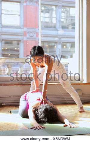 Yoga teacher assisting woman in class - Stock Photo