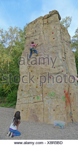 little boy climbing roped up in a professional climbing wall being watched by a girl - Stock Photo