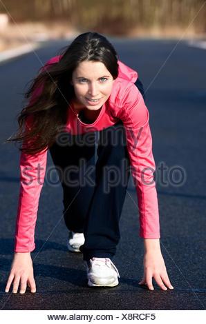 Hübsche junge Frau befindet sich in Startposition für einen Sprint - Stock Photo