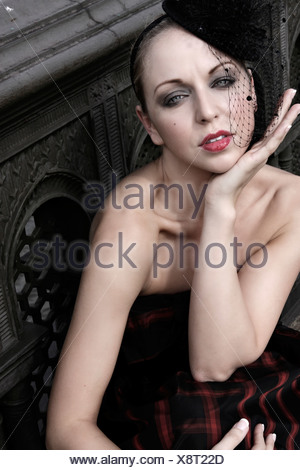 Female fair hair off her face, wearing a pill box hat black netting and strapless dress, smoky eyes make up and red lipstick, - Stock Photo