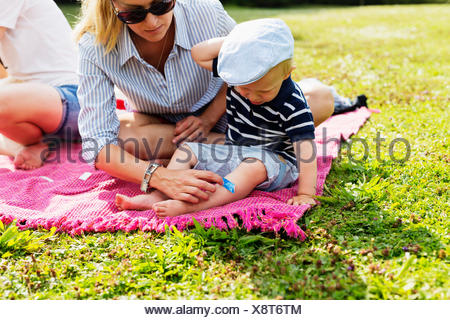 Mother putting bandage on son's leg during picnic in park - Stock Photo