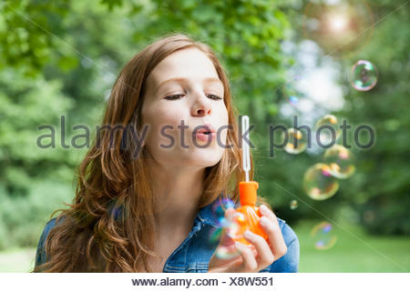 Young woman blowing bubbles in garden - Stock Photo