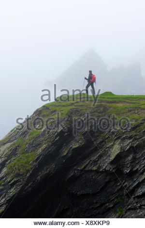 United Kingdom, Scotland, Shetland Islands, Senior woman standing on grassy cliff - Stock Photo