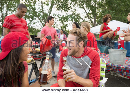 Friends talking at tailgate barbecue in field - Stock Photo