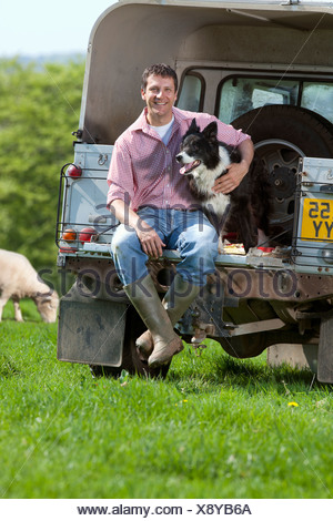 Portrait of shepherd and dog sitting on tailgate of truck in field - Stock Photo