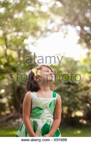 Young girl in garden, wearing flower in her hair - Stock Photo