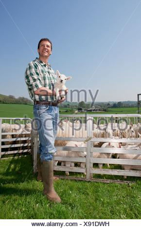 Smiling shepherd holding lamb in pasture - Stock Photo