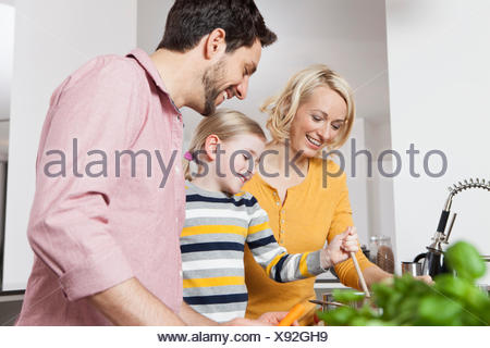 Mother, father and daughter cooking in kitchen - Stock Photo