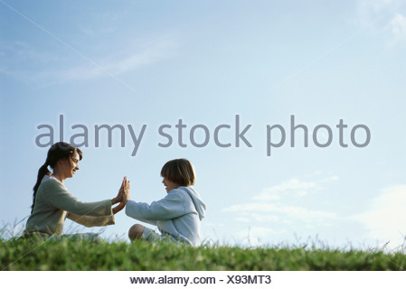 Brother and sister playing clapping game outdoors - Stock Photo