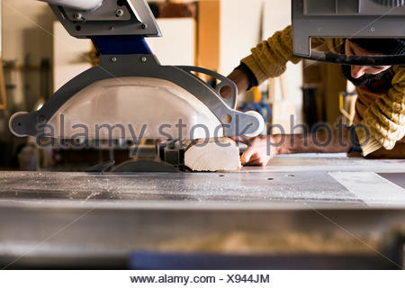 Carpenter cutting wood using table saw in workshop - Stock Photo