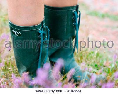 Sweden, Bohuslan, Tjorn, Woman wearing rubber boots in meadow - Stock Photo