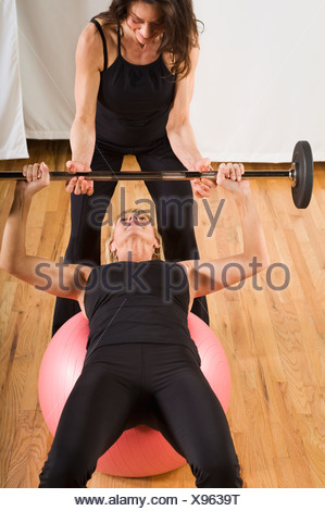 Trainer assisting woman lifting barbell - Stock Photo