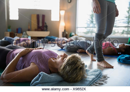 Women laying supported corpse pose in restorative yoga - Stock Photo