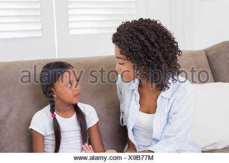 Pretty mother sitting on the couch scolding her daughter - Stock Photo