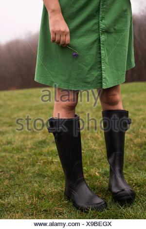 Woman wearing wellington boots, holding a violet flower - Stock Photo