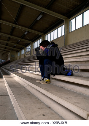 Boy sitting on staircase in depression - Stock Photo