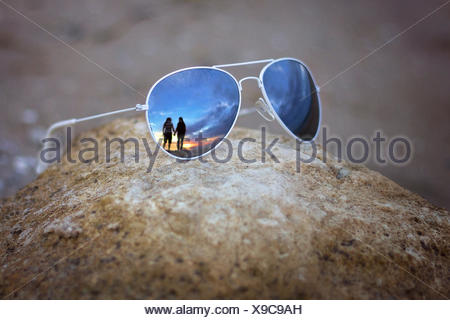 Reflection of couple in sunglasses - Stock Photo